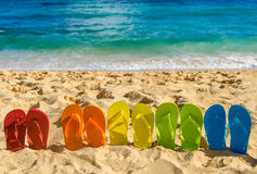 Colorful flip flops on the sandy beach Royalty Free Stock Photography