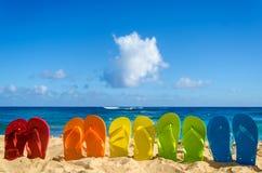 Colorful flip flops on the sandy beach Royalty Free Stock Photos