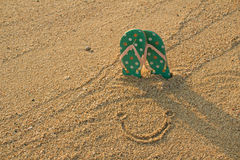 Colorful flip flops and smile icon on white sand beach Royalty Free Stock Images