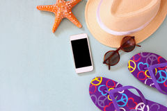 Colorful flip flops, starfish, cellphone, fedora hat and sunglasses on wooden background Royalty Free Stock Photo