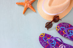 Colorful flip flops, starfish, shells, fedora hat and sunglasses on wooden background Stock Image