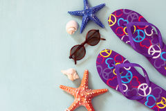 Colorful flip flops, starfish, shells and sunglasses on wooden background Stock Photos