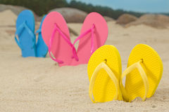 Colorful flip flops on white beach sand. Picture of colorful flip flops on white beach sand Royalty Free Stock Image