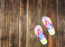 Colorful flip flops on wooden deck. summer background Stock Photos