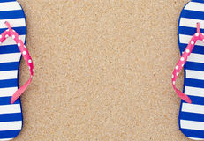 Colorful flipflop pair on beach sand. Colorful flipflop pair as a frame on beach sand royalty free stock image
