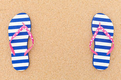 Colorful flipflop pair on beach sand Royalty Free Stock Photo