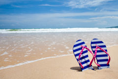 Colorful flipflop pair on sea beach. Concept stock photography