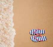 Colorful flipflop pair on sea beach. Top view royalty free stock photos
