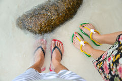 Colorful flipflop sandals. On sea beach royalty free stock images