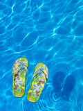 Colorful flipflops floating in a swimming pool Royalty Free Stock Photos