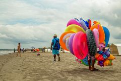 A colorful floater salesman walking on a beach royalty free stock photography