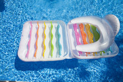 Colorful floating air mattress in swimming pool at summertime as Royalty Free Stock Photos