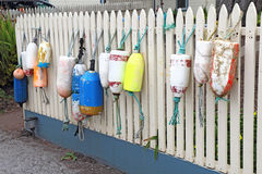 Colorful floats and buoys hanging from a fence Royalty Free Stock Images