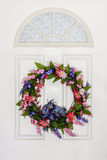 Colorful Floral Summer Wreath Hanging on White Door. Summer wreath of flowers on white Colonial style door.  Made up of  daisies,  lilies, and tiny flowers of Royalty Free Stock Photo