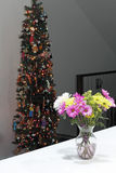 Colorful Flower Bouquet and Christmas Tree. Inside a home at night a beautiful floral bouquet in a vase with a decorated a Christmas tree. Vibrant flowers stock photo