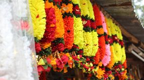 Colorful flower garlands hanging on street shop. In front of temple, Street shops selling plastic and real flower garlands in india Royalty Free Stock Photography