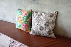 Colorful flower pattern throw cushion on brown seating Royalty Free Stock Photos