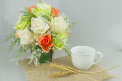 Colorful flower in vase with coffee on gray background. Royalty Free Stock Photography