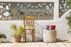 Colorful flowerpots and chair in the streets of Karpathos, Greece. Colorful flowerpots and chair on street of typical greek traditional village with white houses royalty free stock images