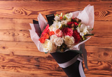 Colorful flowers bouquet with a card on wooden background Royalty Free Stock Image