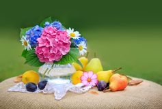 Colorful Flowers Bouquet In Glass Vase And Fresh Mixed Fruits . Royalty Free Stock Photos