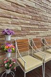 Colorful flowers chair and stone wall Stock Images