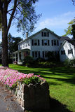 Colorful flowers and classic New England home. Stone wall in Somesville, Maine,Mount Desert Island, Acadia National Park stock image