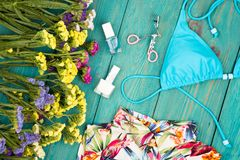 Colorful flowers, dress, swimsuit, cosmetics makeup, bijou and essentials on blue wooden background. Travel concept - summer women& x27;s fashion with colorful Royalty Free Stock Photo