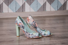 Colorful flowers female stylish shoes on the wood floor. Royalty Free Stock Photos