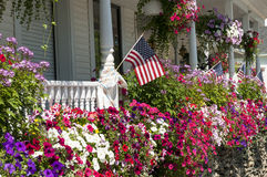 Flags and flowers on house porch. American flags and flower boxes and pots on a New England house porch Stock Photos