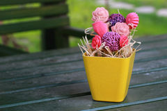Colorful Flowers made of Soaps. Based on green wooden garden table Stock Photo
