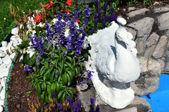 Colorful flowers and marble sculpture in Dolomity mountains, Italy Royalty Free Stock Photo