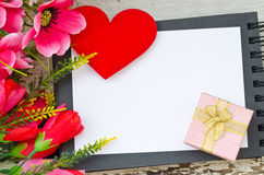Colorful flowers ,red heart and gift box on open book Royalty Free Stock Images