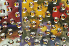 Colorful flowers through water drops on glass Stock Images
