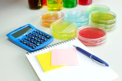 Colorful fluid and note book in glass ware Stock Photography
