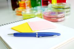 Colorful fluid and note book in glass ware Stock Photos