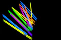Colorful fluorescent light neon big glow stick on mirror reflection black background. Colorful fluorescent light neon glow stick on mirror reflection black stock photos