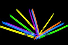 Colorful fluorescent light neon big glow stick on mirror reflection black background. Colorful fluorescent light neon glow stick on mirror reflection black stock image