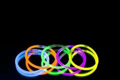Colorful fluorescent light neon glow stick bracelet strap wristband on mirror reflection black background. Yellow Blue pink orange green violet glow sticks royalty free stock photo