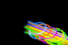 Colorful fluorescent light neon glow stick bracelet strap wristband and tubes on mirror reflection black background. Yellow Blue pink orange green violet glow stock image