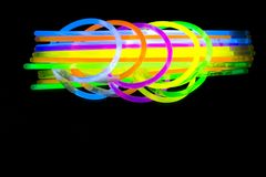 Colorful fluorescent light neon glow stick bracelet strap wristband and tubes on mirror reflection black background. Yellow Blue pink orange green violet glow stock photos