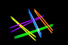 Colorful fluorescent light neon big glow stick on mirror reflection black background. Colorful fluorescent light neon glow stick on mirror reflection black stock photography