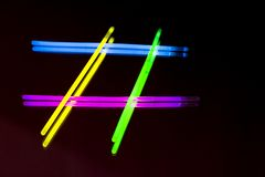 Colorful fluorescent light neon big glow stick on mirror reflection black background. Colorful fluorescent light neon glow stick on mirror reflection black royalty free stock images