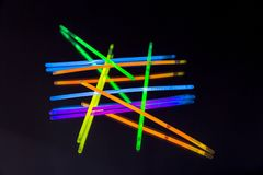 Colorful fluorescent light neon big glow stick on mirror reflection black background. Colorful fluorescent light neon glow stick on mirror reflection black stock images