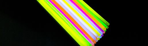 Colorful fluorescent light neon big glow stick on mirror reflection black background. Colorful fluorescent light neon glow stick on mirror reflection black royalty free stock photo