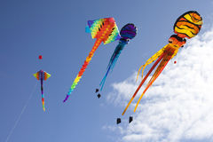 Colorful flying kites against a blue sky Stock Images