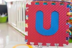 Colorful foam puzzle letters, alphabet U Stock Image
