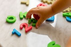 Colorful foam puzzle letters and numbers in kid`s hands on a light table. Baby puts puzzle of letters and numbers. Close-up Stock Photo