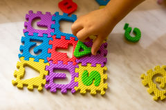 Colorful foam puzzle letters and numbers in kid`s hands on a light table Stock Photos