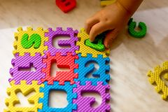 Colorful foam puzzle letters and numbers in kid`s hands on a light table. Colorful foam puzzle letters and numbers in a kid`s hand on a light table. Preparing Stock Photography